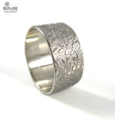 A 14k white gold ring band features a beautiful floral pattern engraved in a romantic modern style.  The ring Texture Stripes and floral design   encircles the band with nature inspired beauty