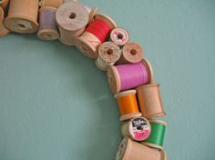 Been looking for ideas for my old wood spools.  I love this colorful vintage spool wreath! #Thread #Sewing #Craft