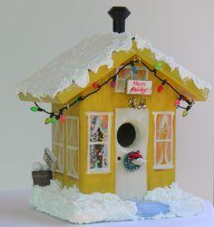 Amarillo decorativo Birdhouse de Navidad con las luces que destellan.  Árbol de Navidad en la ventana, muñeco de nieve y mucho más