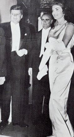 A simple white satin sheath gown was worn by Jacqueline Kennedy at a dinner party in the Greek Embassy hosted by Greece's Prime Minister Constantine Caramanlis, at center.                ❁❤❃❤❁❤❁❤❁❤❁❤✾ http://en.wikipedia.org/wiki/John_F._Kennedy http://en.wikipedia.org/wiki/Jacqueline_Kennedy_Onassis   http://en.wikipedia.org/wiki/Konstantinos_Karamanlis
