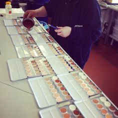 Kryolan staff filling palettes. Lots of products are hand made.