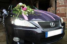 Déco voiture des mariés : tulle et composition de fleurs et feuillages sur le capot + ballons en forme de cœur et nœuds de tulles accrochés à l'arrière après la sortie d'église...
