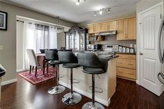 Kitchen with a gorgeous granite island and upgraded stainless steel appliances . Diamond Realty & Associates Ltd. Corner Pantry, Maple Cabinets, Large Family Rooms, Basement Bedrooms, Selling Real Estate, Private Room, Stainless Steel Appliances, Floor Finishes, Gas Fireplace