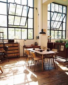 This is the perfect working atelier for any creative work! Love the big windows with black frames and the different wood textures.