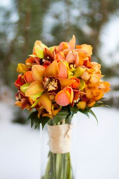 Winter wedding in Colorado with charming splashes of orange in this #bouquet!  Photography by Michele DeVries  of http://inphotography.net, Floral Design by bloomflowershop.com