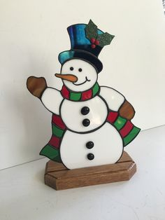 This cute snowman is all bundled up for the winter wearing a black iridescent top hat with holly and berries, and a scarf made of red and green stained glass. His nose is orange stained glass and is a