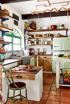This quant little farmhouse style kitchen on a horse ranch in Florida is cozy and colorful. A Big Chill Retro refrigerator and dishwasher in mint green add cool color to the space.