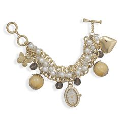 "8"" + 1"" extension 4 strand gold tone and plastic pearl fashion charm toggle watch. The watch face charm is 20mm x 28mm oval gold tone with swarovski crystal accents The other charms include a 23mm gold tone heart, 21mm gold tone butterfly, two 20mm glass beads and 4 10mm smoky faceted plastic bea..."