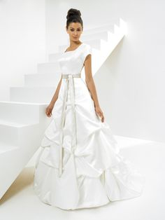 Description: This wedding dress features scoop neckline and short sleeves. Bustier bodice decorated by hand made embroidery and beading work. Chapel train. A line silhouette. Nice modest gown to be chosen for formal weddings.    Fabric: ...