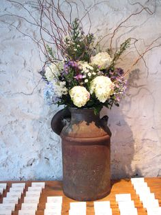 old milk can; different flowers, cute idea though-could be at entrance of the isle on each side.