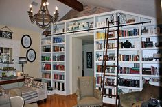 A rolling library ladder gives easy access to this reader's wall of DIY custom bookshelves. | thisoldhouse.com