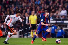 Andres Iniesta of FC Barcelona conducts the ball past Carlos Soler (L) of Valencia CF during the La Liga match between FC Barcelona and Valencia CF at Camp Nou stadium on March 19, 2017 in Barcelona, Catalonia.