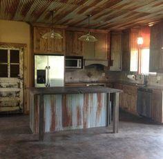 Rustic kitchen with old door for pantry door, custom made island, tin ceiling.