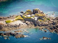 Fort Clonque is the most remarkable of the great mid-Victorian harbour works off Alderney, built to protect the Channel Islands from capture by the French. At high tide the fort is cut off from the rest of the island. Large Holiday Homes, Guernsey Channel Islands, Unusual Hotels, Amazing Hotels, Amazing Places, Beautiful Places, Stay In A Castle, Old Fort, Famous Castles