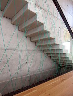 Particolare scala in cemento con una parete di corda con un disegno geometrico, colore blu turchese.