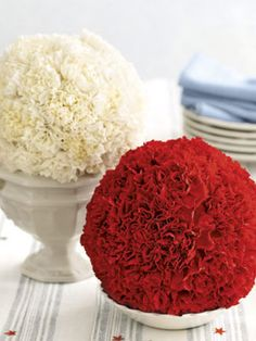 """4th of July Carnation Balls    1) Saturate a 3-inch sphere of floral foam with cool water.  2) Insert short carnation stems — cut to an inch below the calyx  in a concentric, coiling pattern until the sphere is almost covered.   3) Display carnation balls individually, or cluster balls of varying sizes & color — on a favorite vase or tray to create a centerpiece.  4) Place sphere with its """"bald spot"""" in a saucer of cool water; refresh daily and it will last a week."""