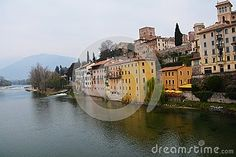 Yellow houses on the shore of the Brenta river in the old town of Bassano del Grappa, Veneto, Italy.