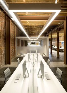 A long table has rows of computers and chairs. A long rectangular light fixture hangs above.