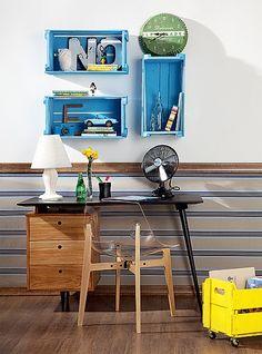 Pintadas com tinta látex azul e pregadas na parede, as caixas de feira organizam e dão charme ao escritório