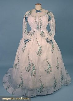"""PRINTED VOILE DAY DRESS, 1860s Lot: 779  2-piece white w/ green & brown floral pattern, trimmed w/ aqua ribbon & lace, DLM, B 40"""", W 29"""", Front L 42"""", Back L 53"""", (period mends in skirt)"""