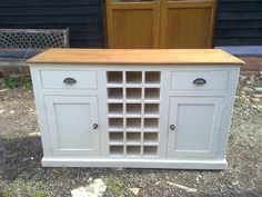 Reclaimed pine sideboard/dresser with wine rack, painted in Farrow & Ball 'new white' with light distress finish with black/gray metal pull-handles & knobs.