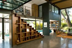 """A step up in book storage, these Japanese-inspired """"Tansu Stairs"""" were designed by Steven Ehrlich, FAIA - Ehrlich Architects and hand crafted by David Albert. They're set in a sustainable residence just one kilometer from the Pacific Ocean, and are built to reflect the bohemian spirit of Venice, Calif. A staircase bookcase is a great space saver in a home like this one, built on a narrow lot."""