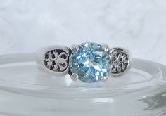 This stunning ring is made of 925 Sterling Silver.  It has a prong set 7 mm Round Cut genuine Sky Blue Topaz gemstone.  It has a motif design on the shank.    It is a size 7.
