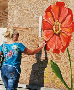 She travels across the U.S. and selects derelict buildings, then decorates them with paintings of a single flower.  Mandy with one of Andrea LaHue Describe your pin…flowers.
