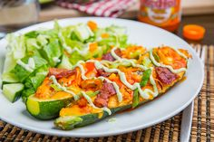 Buffalo Chicken Stuffed Zucchini topped with Melted Cheddar, Bacon and an Avocado Blue Cheese Dressing
