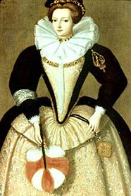 Later Tudor fashion, cartwheel farthingale over a bolster, stiffened stomacher, padded sleeves, and a ruff.