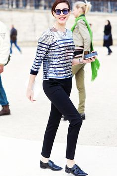 A silver long sleeve striped top is paired with black sleek trousers and black oxfords