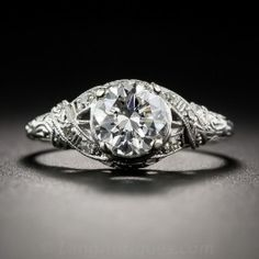 The sophisticated design of this Art Deco dazzler incorporates neoclassical design motifs, most prominently, crossed ribbons set with diamonds on each shoulder. The gorgeous, icy-white, transitional round brilliant-cut diamond (post-dating the vintage of the mounting), weighs 1.14 carats and is accompanied by a GIA Diamond Grading Report, stating: E color - SI1 clarity. Decorative piercing and hand-engraving  add the finishing touches to this stunning engagement ring. Currently ring size 6…