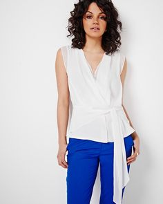 The feminine chiffon blouse gets a fresh update with a wrap front and self tie at the front. Perfect to elevate a pant and blazer combo.<br /><br />- Sleeveless<br />- V-neckline<br />- Side invisible zipper<br />- Pleat at back<br />- Front tie