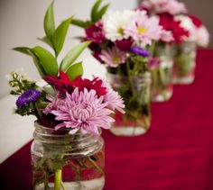 Cheap fresh flowers and reusable mason jars - make for a great table centerpiece. Very Affordable!