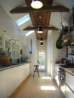 another narrow kitchen- they are starting to grow on me! What about making one wall only a half wall and so that counter top (with two heights like the Caroline Court house) can double as a bar and the room on the other side is dining room (easy to pass food through) or family room (open feel)