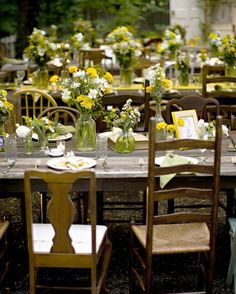 The centerpieces at this wedding consisted of a mix of white, green, and yellow wildflowers and plants in clear glass vases of various sizes.