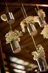 Vases suspended at different heights with flowers. Tin cans + baby's breath.