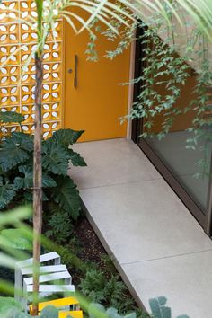 Casa Jardins (Casa 10x38) / CR2 Arquitetura #entry #entrance #door #doorway #wall #hall #corridor #concrete #outdoor #yard #backyard #green #patio #terrace #cobogo #yellow @ElementoV @clarareynaldo