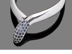A sapphire and diamond-set bangle The hinged figure-of-eight bangle, polished to one side and brushed to the opposing side, the clasp set with circular-cut sapphires and a brilliant-cut diamond of blue tint, accented with a brilliant-cut diamond push piece