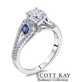 Love this exquisite #Engagement Ring from the #ScottKay Radiance Collection. A round cut center stone with beautiful sapphire accents on the side.