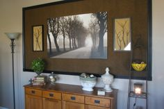 The wall was boring so, I put textured fabric behind the large picture, shadow boxed some cherry tree branches- with a lighter fabric behind those and framed the entire thing with molding I painted black.