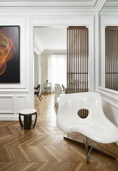 Allowing those original molding details to shine through, the entrance into the dining and living area is kept simple and modern with a Charles et Ray white abstract Eames chair and a walnut wood sculpture in the doorframe.