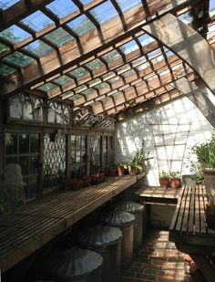 The interior of the greenhouse is a workman-like space with slated benches and galvanized bins for holding potting compost. The side windows...