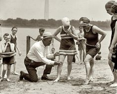 June 30, 1922. Officer measuring the distance between knee; suits not to be over six inches above the knee.
