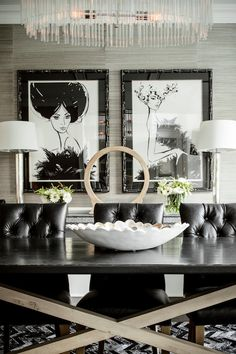 Beautiful dining room features oval crystal chandelier over trestle dining table surrounded by black leather tufted dining chairs, Restoration Hardware Martine Leather Side Chairs over black and white chevron rug.