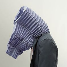 A pleated hood covered in thermochromic pigments gradually changes colour with fluctuations in body heat, which can occur when the wearer is shy or embarrassed.