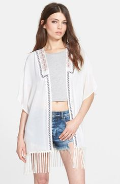 Colorful geo embroidery frames the open front of a lightweight duster trimmed with slender fringe at the hemline.