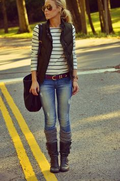 Black puffer vest with striped 3/4 sleeve top, medium/light destroyed jeans, leg warmers and boots. Complete with low pony and chic sunglasses.