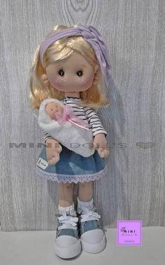 Esta es Lola una moderna mamá a la que le encanta pasear por la ciudad con su bebé.  Toda su ropa y complementos están hechos a mano a medida para ella. Zapatos estilo Converse en jean y foamy. Camiseta y pañuelo de algodón. Falda de jeans con puntilla de algodón. Lleva braguitas y calcetines. Bebé hecho a mano para ella.  Incluye peana de madera pintada y decorada a mano a juego con ella.  Esta muñeca no está recomendada para niñ@ menores de 3 años por contener piezas pequeñas. Esta muñeca…