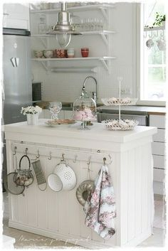 Short on cabinet space? Do what the homeowners of this Country Cottage did: add a board with hooks to your kitchen island for hanging pots and frequently used utensils !